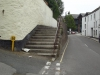 The Parade, Malpas Road. Granite steps at both ends plus handrails. Ceramic tiled surface with capped wall. Opposite the rear of the bakery.